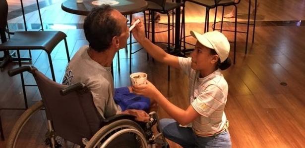 """Funcionária do McDonald""""s Lawane Rodrigues ajuda José Avelino a comer sorvete em shopping center de Uberlândia (MG) - Thiago Ferreira/Divulgação"""