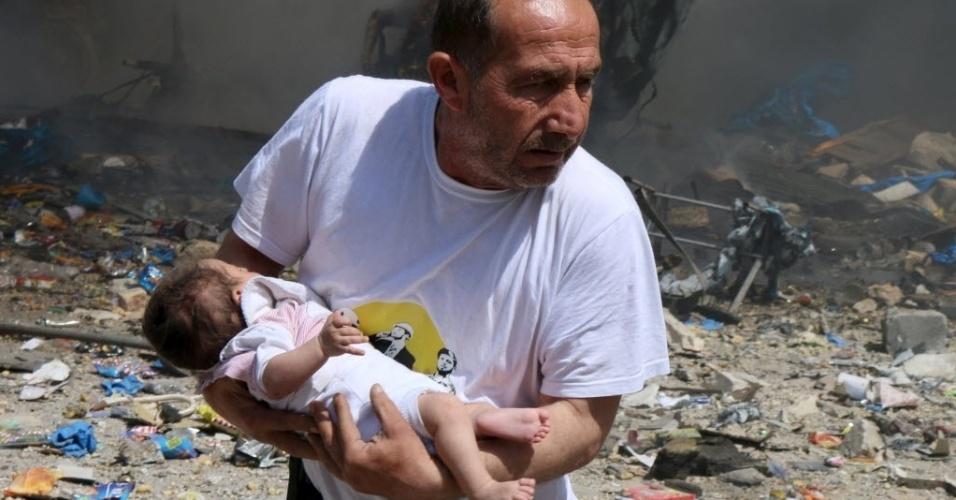 3.jun.2015 - Homem segura um bebê que sobreviveu a um ataque feito por forças leais ao ditador sírio Bashar Assad, em Aleppo, Síria. Pelo menos 24 pessoas morreram, entre elas oito crianças, durante os bombardeios desta quarta-feira (3)