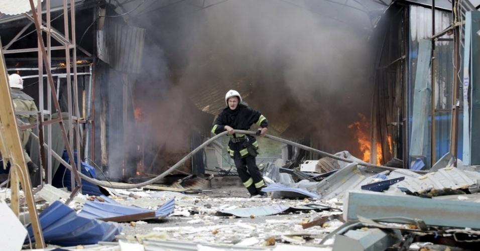 3.jun.2015 - Um bombeiro trabalha para extinguir um incêndio em um mercado danificado por bombardeios, em Donetsk, Ucrânia. O governo acusou nesta quarta-feira (3) os rebeldes pró-russos do leste do país de lançarem