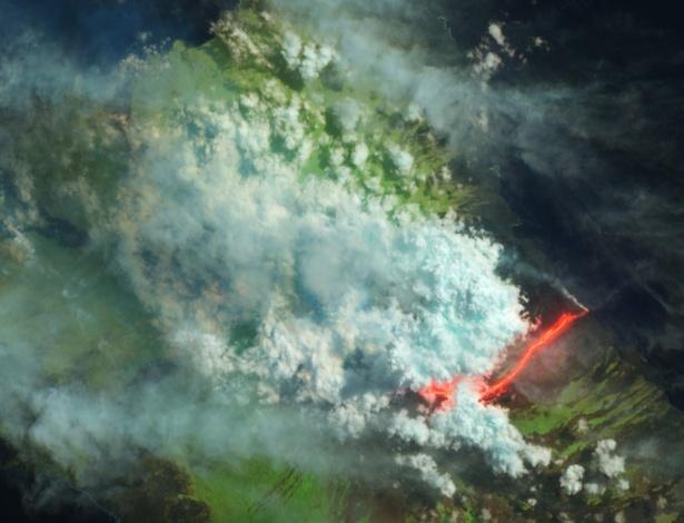 3.jun.2015 - Imagem divulgada pela Nasa (agência espacial norte-americana) capta o vulcão Wolf, o mais alto pico nas ilhas Galápagos, que entrou em erupção pela primeira vez há 33 anos. Apesar das nuvens, o satélite Earth Observing-1 registrou a imagem da lava fluindo do vulcão para o oceano em 28 de maio. A coloração artificial da foto combina imagens de ondas curtas de infravermelho, próximo de infravermelho e luz verde. As nuvens aparecem branco-azuladas, enquanto a água é vista em azul escuro. As áreas cobertas por mata surgem em verde. Os fluxos de lava são vistos em marrom, enquanto a lava incandescente é laranja e vermelha. O vulcão Wolf está localizado na parte mais ao norte de Isla Isabela, a maior ilha em Galápagos. Segundo autoridades locais, o fluxo de lava não ameaça uma colônia de iguanas rosa que vivem ali perto, uma espécie única