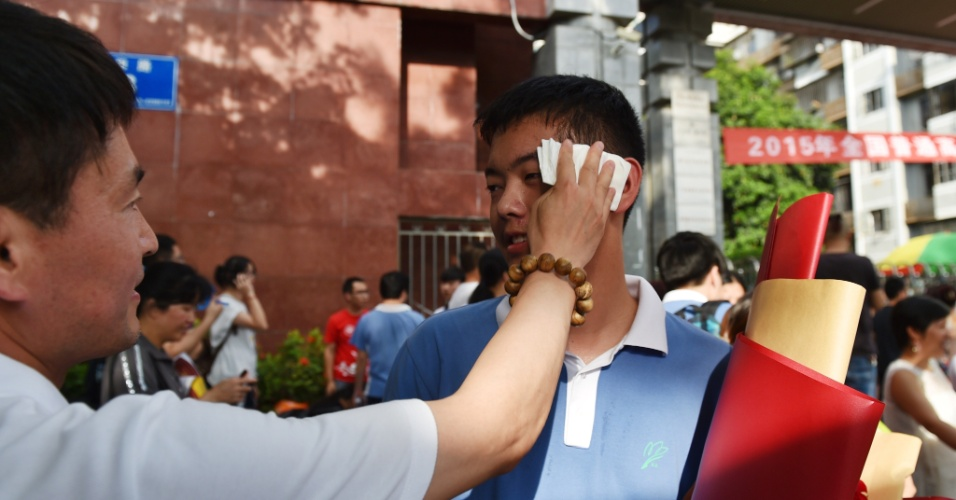 """8.jun.2015 - Pai limpa suor do rosto do filho após o """"gaokao"""", considerado a maior prova de acesso à universidade do mundo, que tem duração de dois dias. Mais de nove milhões de estudantes fizeram os exames neste ano"""