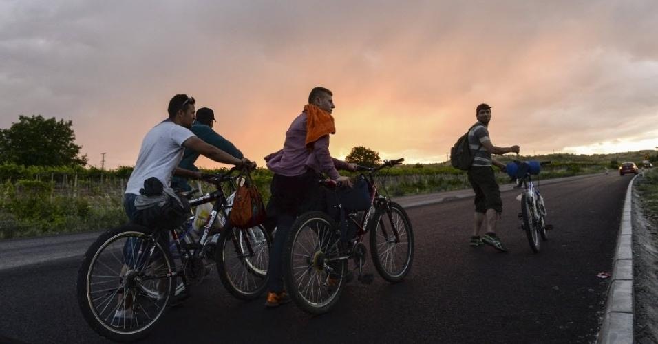 9.jun.2015 - Migrantes fogem da Síria de bicicleta por uma via pouco trafegada para tentar ingressar na União Europeia, perto da cidade de Veles, na Macedônia. Após várias mortes ocorridas durante as tentativas de subir em trens e das prisões, imigrantes têm mudado seus meios de transporte para deixar o país