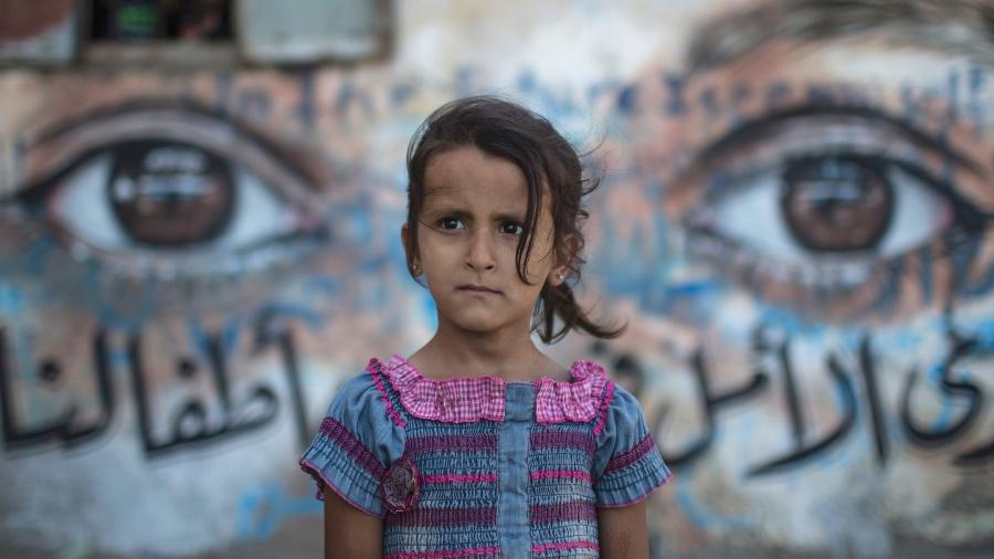 10.jun.2015 - Menina palestina é fotografada em frente a mural feito nas paredes das casas destruídas durante ofensiva israelense na faixa de Gaza - Wissam Nassar/Xinhua