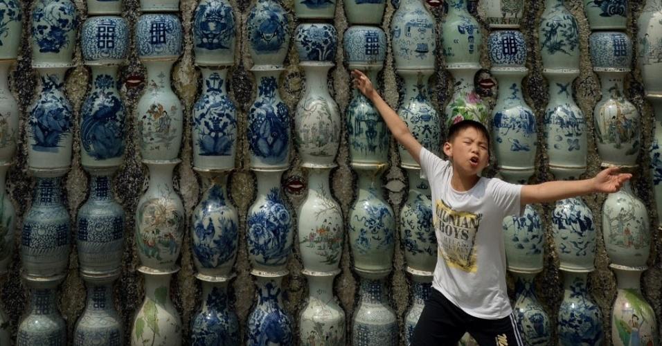 11.jun.2015 - Menino brinca em frente a casa feita com centenas de vasos, tigelas e pratos de porcelana embutidos nas paredes, em Tianjin, na China