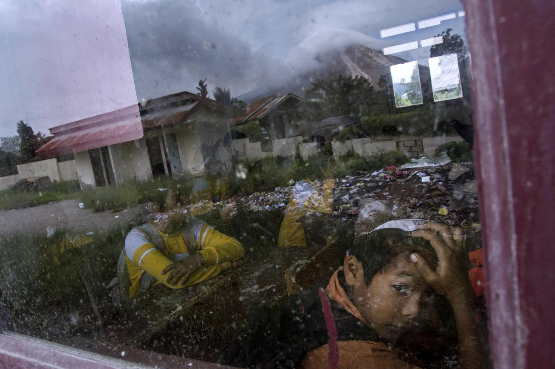 12.jun.2015 - Estudante indonésio observa a paisagem, enquanto o vulcão Sinabung, refletido na janela, lança cinzas vulcânicas na província de Sumatra do Norte, nesta sexta-feira (12). Cerca de 3.000 pessoas foram evacuadas de suas casas depois da Indonésia atualizar o alerta de vulcões em Sumatra para o nível mais alto possível