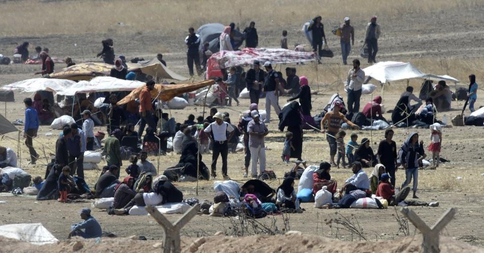 12.jun.2015 - Refugiados sírios acampam no lado turco da fronteira, em Akçakale, a poucos quilômetros da cidade síria de Tal Abyad, nesta sexta-feira (12). A Turquia diz estar tomando medidas para limitar o fluxo de refugiados sírios para seu território, após a entrada de milhares nos últimos dias devido a confrontos entre curdos e o Estado Islâmico. A Turquia já recebeu 1,8 milhão de refugiados desde o início do confronto na vizinha Síria, em 2011