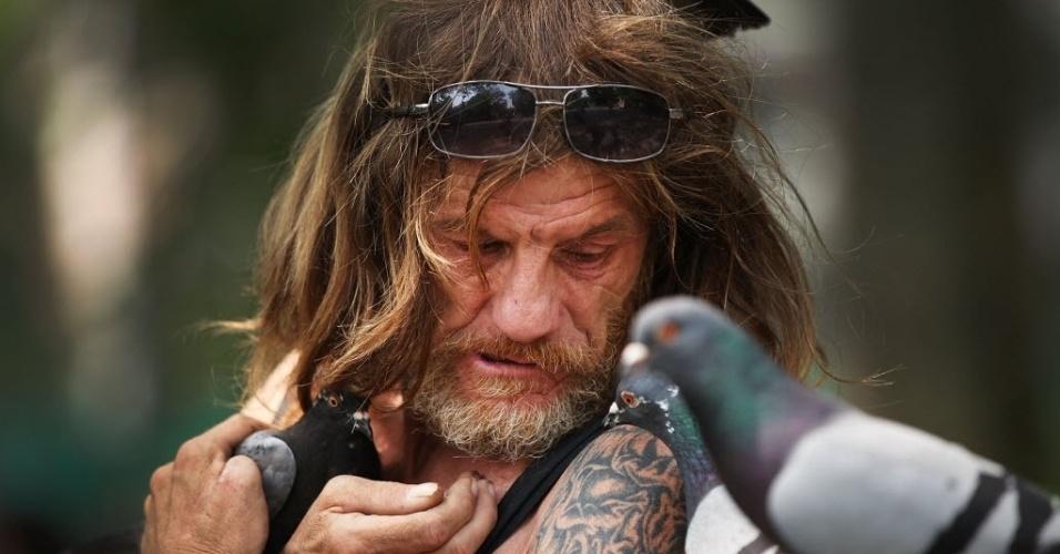 12.jun.2015 - Larry, um aficionado por pássaros, alimenta um pombo no Washington Square Park em um dia quente em Manhattan, na cidade de Nova York (EUA), nesta sexta-feira (12). As temperaturas na