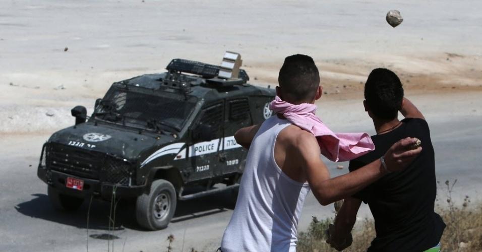 12.jun.2015 - Manifestantes palestinos lançam pedras contra um veículo das forças de segurança israelenses durante confrontos do lado de fora da prisão militar israelense Ofer, próximo à cidade de Betunia, na Cisjordânia, após manifestação contra o confisco de terras palestinas e a expansão de assentamentos