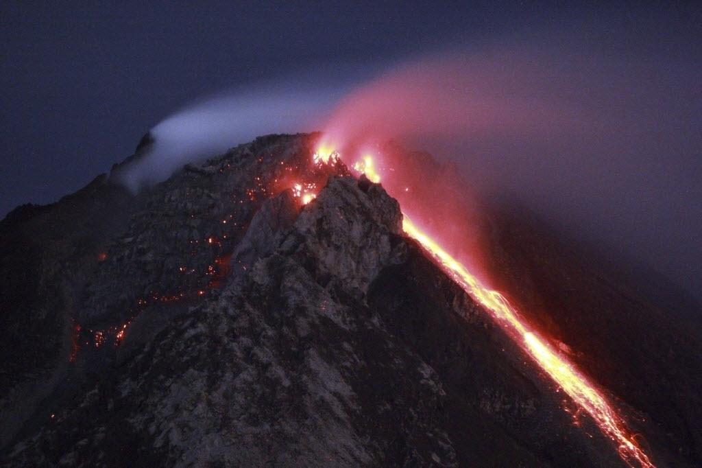 12.jun.2015 - Monte Sinabung expele lava na vila Tiga Serangkai, na Indonésia. Mais de 2.700 pessoas que residem perto do vulcão tiveram que deixar suas casas em 4 de junho. O alerta sobre o Monte Sinabung está no nível mais alto. Em fevereiro de 2014, 16 pessoas morreram e 2.000 ficaram desabrigadas