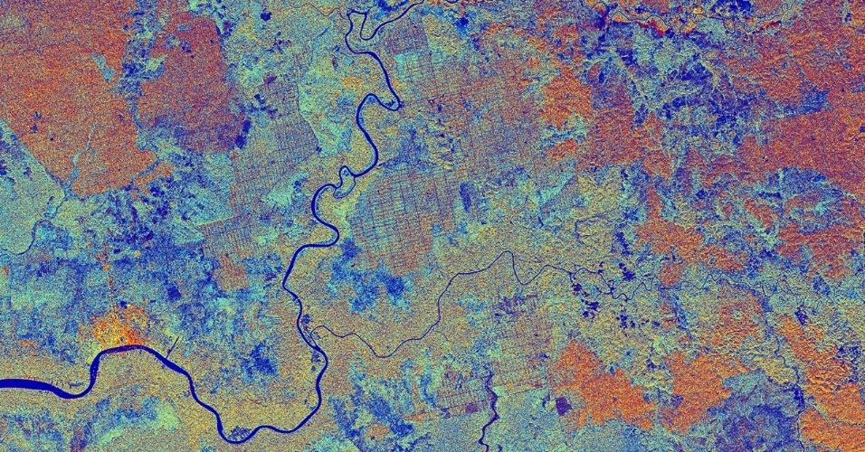 12.jun.2015 - Satélite captura imagem da província de Kalimantan Central, na Indonésia, na ilha de Bornéu. Rodeada pelo mar do sul da China, o local já fez parte da Ásia, mas o aumento dos níveis do mar após o final da última Idade do Gelo deixou submersa as áreas mais baixas. Sua floresta tropical é a mais antiga e mais diversificada do mundo. Na imagem, é possível ver o rio Sampit no canto inferior esquerdo. A área é dominada por florestas, onde o solo encharcado impede folhas mortas e madeira de se decompor totalmente, criando uma camada de turfa ácida ao longo do tempo. A ilha tem sido afetada pelo extremo desmatamento nas últimas décadas através de exploração madeireira, o desenvolvimento das plantações, mineração e incêndios florestais
