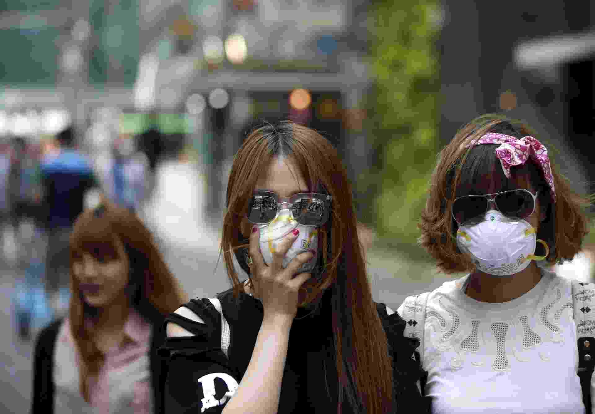 12.jun.2015 - Turistas usam máscaras como prevenção contra a Mers, no distrito comercial de Myeongdong, Seul, Coreia do Sul - Kim Hong-Ji/ Reuters