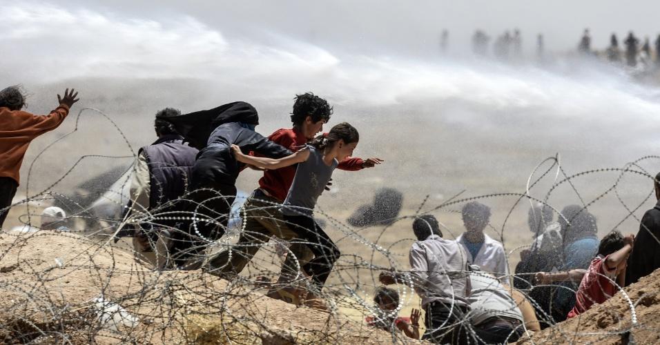 13.jun.2015 - Refugiados sírios fogem de soldados turcos que acionam um canhão de água para afastar os imigrantes das cercas na fronteira de Tal Abyad, em Akçakale, na província de Sanliurfa, fronteira entre Síria e Turquia. Autoridades turcas justificaram a medidas afirmando que precisam limitar a entrada de refugiados sírios em seu terrórios, que aumentou devido às lutas entre curdos e jihadistas. Até agora, a Turquia já recebeu mais de 1,8 milhão de refugiados sírios desde o início do conflito em 2011