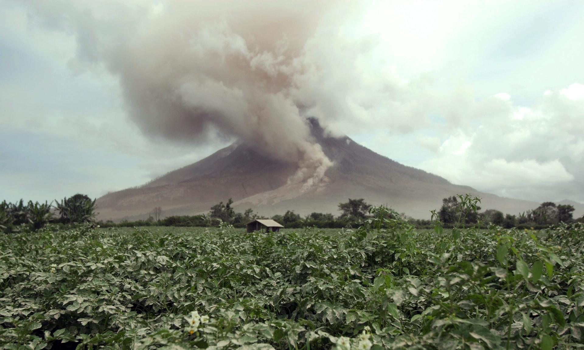14.jun.2015 - Monte Sinabung expele gás vulcânico em imagem realizada na vila de Tiga Serangkai, em Karo, na ilha da Sumatra do Norte, na Indonésia