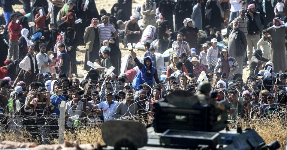14.jun.2015 - Sírios fugindo dos combates em Tal Abyad pedem água ao se concentrarem em posto de controle na fronteira com a Turquia, neste domingo (14), próximo da cidade turca de Akçakale. No sábado, forças de segurança turcas usaram canhões de água e tiros de aviso para afastar refugiados sírios da fronteira, separado por cercas de arame farpado. Tal Abyad é sitiada por exércitos do Estado Islâmico, enquanto é defendida por forças curdas