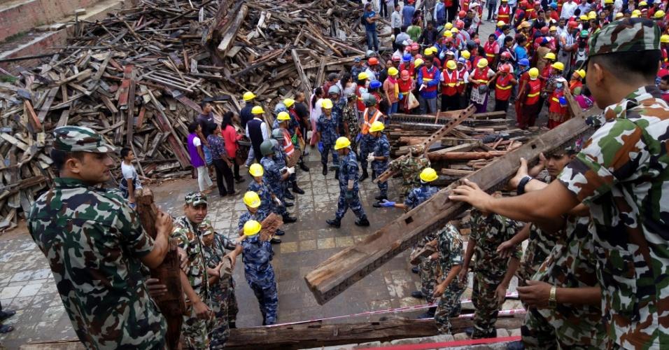 """13.jun.2015 - Policiais e soldados do exército do Nepal carregam traves de madeira que adornavam o tempo Laxmi Narayan para um lugar seguro na praça Durbar, em Katmandu, Nepal. A Unesco informou que aumento sua preocupação com os trabalhos de recuperação após o terremoto e que atribuiu como """"zona de perigo"""" os monumentos listados como patrimônio mundial"""