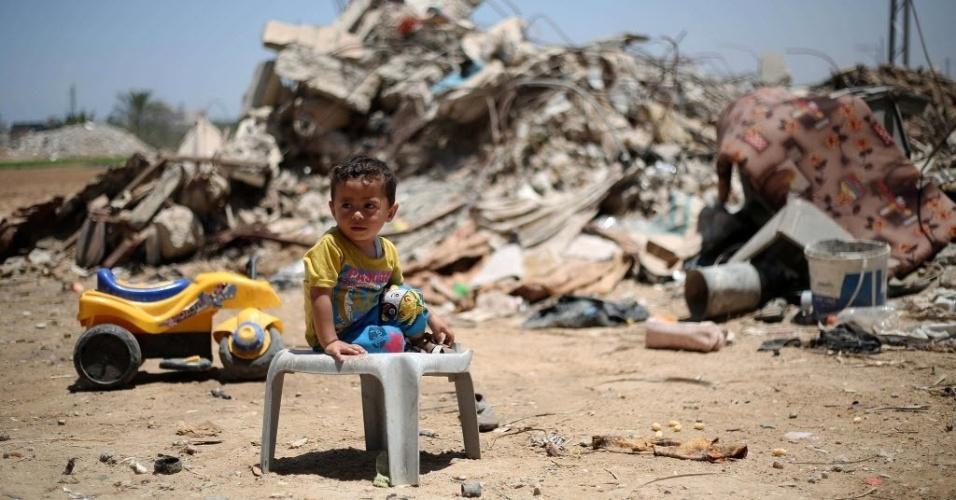 15.jun.2015 - Criança palestina se senta na frente dos escombros de edifícios que foram destruídos durante a guerra de 50 dias entre Israel e o Hamas, entre julho e agosto de 2014, na aldeia de Khuzaa, a leste de Khan Yunis, no sul da faixa de Gaza. Israel bloqueou uma visita de enviado da ONU aos territórios palestinos pouco antes da publicação de um relatório sobre o conflito
