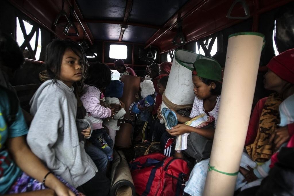 15.jun.2015 - Crianças são evacuadas em caminhão da vila de Kuta Tengah, no norte da província de Sumatra, Indonésia, após um vulcão entrar em atividade na região. Milhares de pessoas já foram levadas para locais seguros
