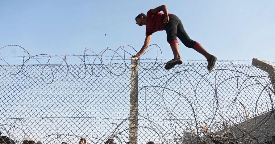 15.jun.2015 - Refugiado pula cerca na fronteira com a Turquia, em Akcake, no sul do país, fugindo dos conflitos entre combatestes curdos e militantes do Estado Islâmico, nesta segunda-feira (15)