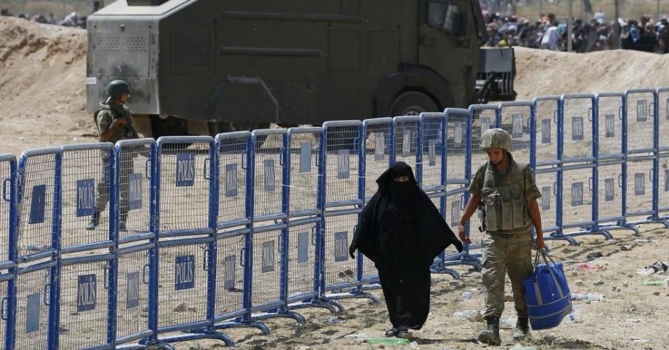 15.jun.2015 - Soldado turco ajuda refugiada síria a levar seus pertences pela fronteira de Akçakale, na província de Sanliurfa, na Turquia. Nas últimas duas semanas, cerca de 15 mil refugiados sírios entraram no país pelo local
