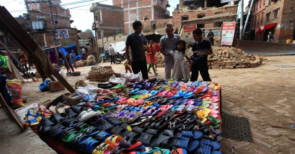 15.jun.2015 - Uma família compra sandálias diante de casas danificadas pelo terremoto em abril, em Bhaktapuri. Segundo as autoridades, mais de 8.000 casas foram danificadas ou destruídas pelo tremor de 25 de abril