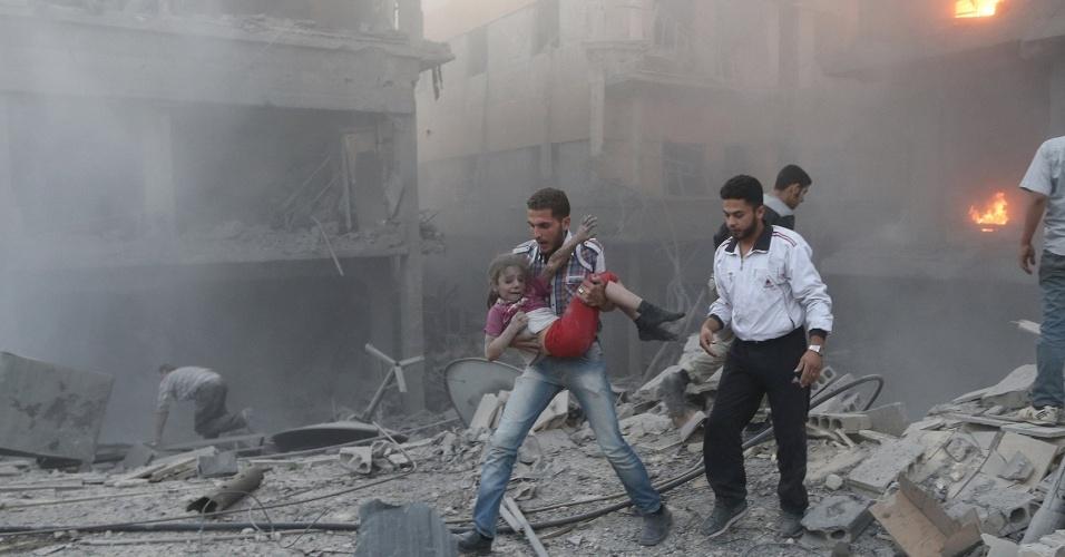 16.jun.2015 - Homem segura uma menina que sobreviveu a um bombardeio realizado por forças leais ao presidente sírio Bashar al-Assad, no bairro de Douma, Damasco (Síria), nesta terça-feira (16)