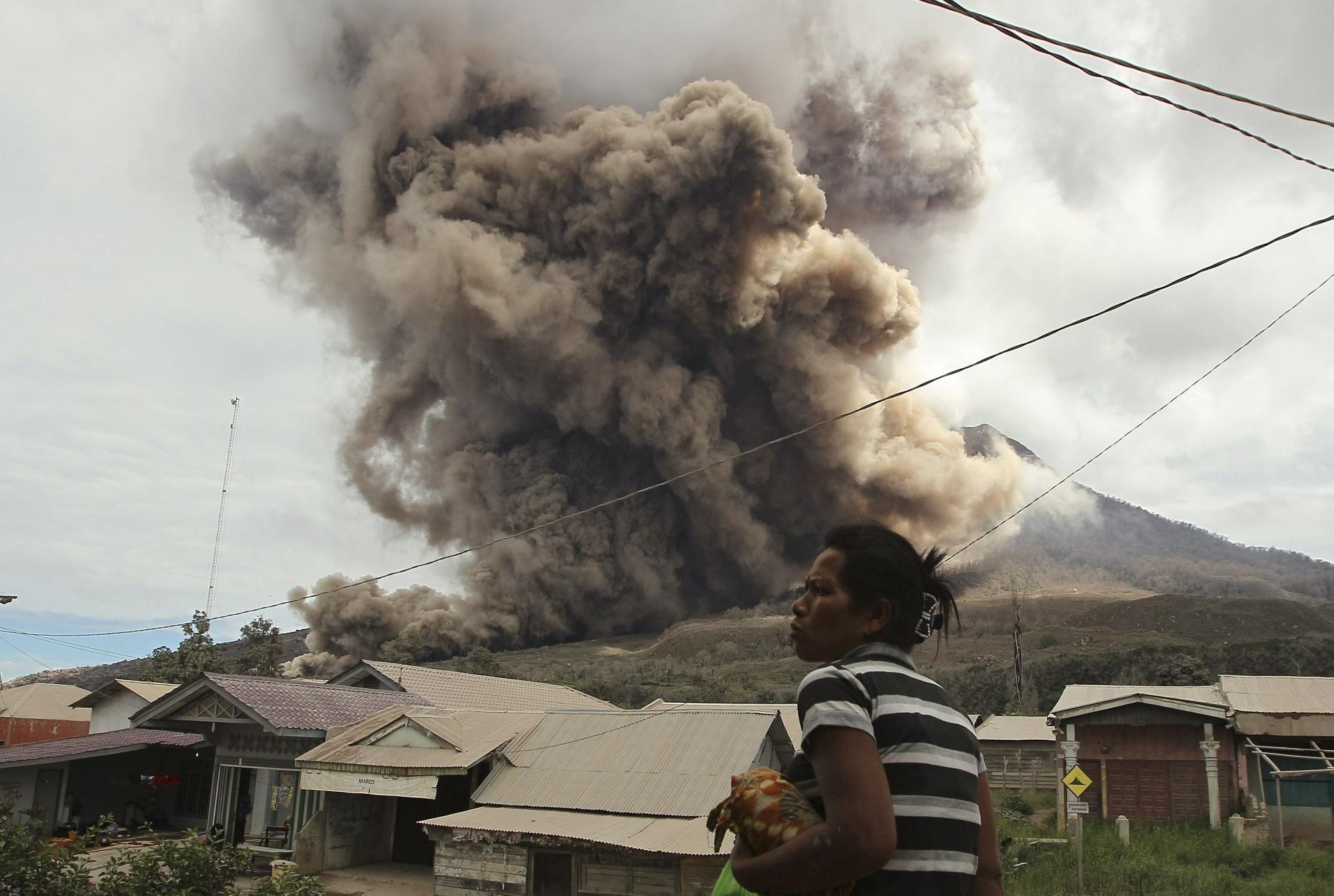 16.jun.2015 - Moradora da vila de Sukanalu, no distrito Karo Regency, observa a erupção do vulcão Monte Sinabung, em Sumatra Norte, Indonésia. Mais de 1.200 moradores de vilas foram retirados da área na ilha de Sumatra, segundo um comunicado oficial, mas muitos residentes ainda se recusam a deixar suas casas