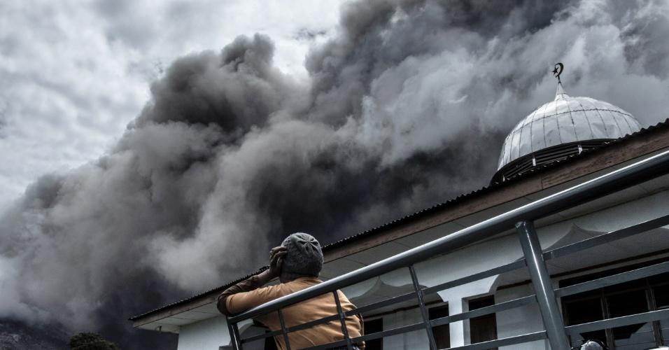 16.jun.2015 - Moradora do distrito de Karo Regency observa erupção do vulcão Monte Sinabung, na província Sumatra Norte, Indonésia.Mais de 1.200 moradores de vilas foram retirados da área na ilha de Sumatra, segundo um comunicado oficial, mas muitos residentes ainda se recusam a deixar suas casas