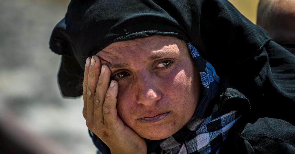 16.jun.2015 - Mulher chora enquanto descansa durante caminho até a cidade de Tel Abyad, após fugir de Maskana, em Aleppo, nesta terça-feira (16). Com uma série de vitórias sobre o Estado Islâmico, curdos da Síria têm se mostrado aliados dos EUA na luta contra jihadistas do Estado Islâmico