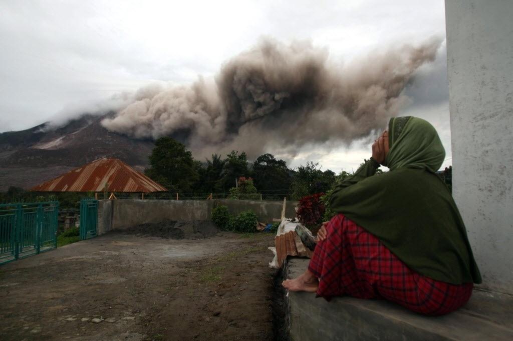 16.jun.2015 - Mulher observa as cinzas lançadas pelo Monte Sinabung, um vulcão de 2.460 metros de altura na ilha de Sumatra, no oeste da Indonésia