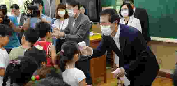 Protegido com uma máscara, o prefeito de Seul mede a temperatura de alunos de escola fundamental - Xinhua