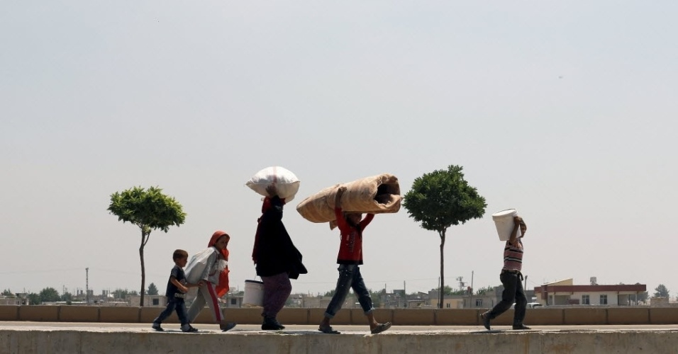 17.jun.2015 - Refugiados sírios caminham até a fronteira da Turquia para retornar às suas casas na cidade síria de Tel Abyad, na província de Sanliurfa. Forças curdas retomaram o controle da região, antes sob o domínio do Estado Islâmico