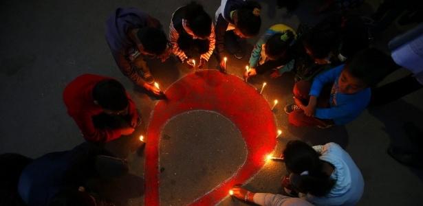 Crianças e mulheres atendidas por centro de reabilitação para soropositivos participam de vigília em Katmandu, no Nepal, em novembro de 2015