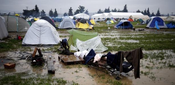 Roupas de refugiados estendidas do lado de fora de tenda montada em meio à lama