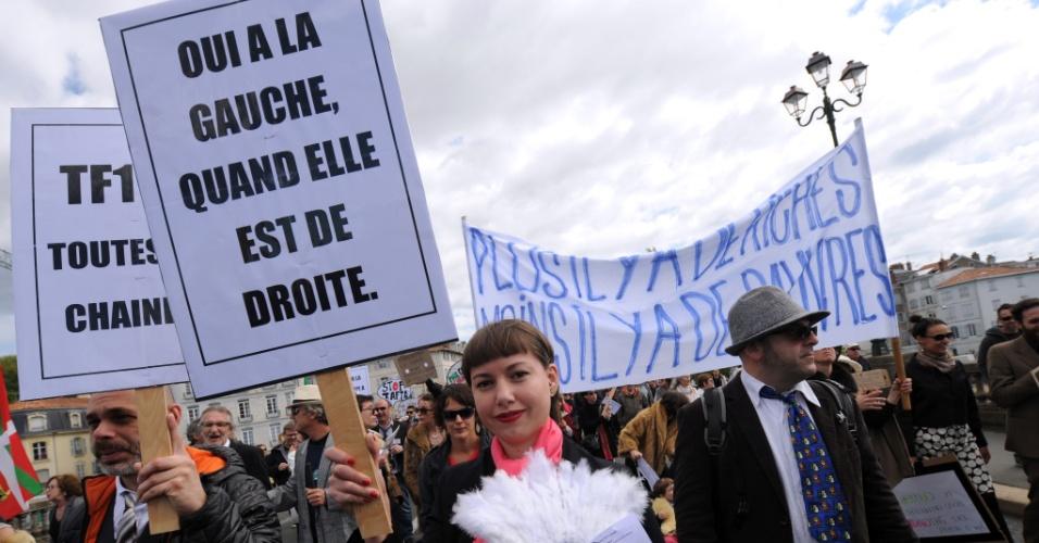 """1º.mai.2016 - Mulher mostra placa com a frase """"Sim para a esquerda quando ela está à direita"""", como membros do movimento """"Bizi!"""" (""""ao vivo"""" em basco) realizam um irônico """"protesto de ricos"""" para marcar o Dia do Trabalho em Bayonne, França. O Bizi! é um movimento anti-globalização do País Basco"""