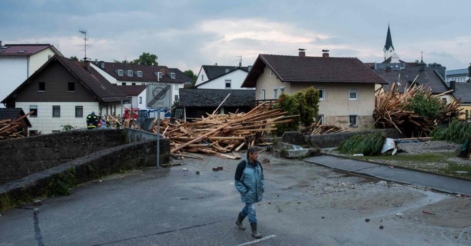 1º.jun.2016 - Um homem caminha entre casas destruídas e troncos que foram arrastados durante enchentes e fortes chuvas em Simbach am Inn, na Alemanha.O nível da água baixou depois de ter alcançado os telhados das casas em algumas regiões. Foi nesta pequena cidade de 10 mil habitantes, perto da fronteira com a Áustria, que os socorristas descobriram em uma casa inundada quatro corpos de mulheres, três da mesma família