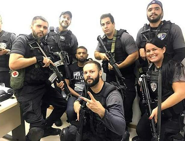 Policiais fardados e armados aparecem sorrindo ao lado de Rogério 157