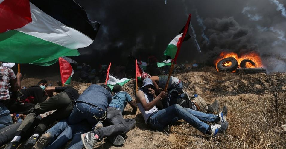 14.mai.2018 - Manifestantes palestinos queimam pneus e se protegem de bombas de gás lançadas por forças israelenses na Faixa de Gaza