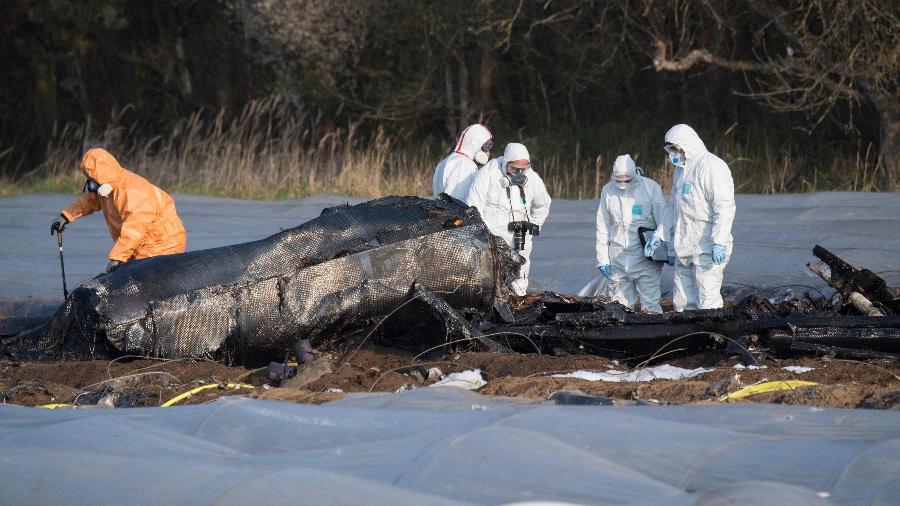 1.abr.2019 - Peritos e policiais inspecionam os restos queimados de um pequeno avião que caiu na Alemanha - Boris Roessler/dpa/AFP