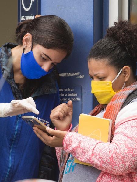 8.mai.2020 - funcionária da Caixa Econômica Federal auxilia cliente na porta de agência do banco em Taboão da Serra, na Grande São Paulo - Mister Shadow/ASI/Estadão Conteúdo