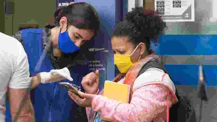 8.mai.2020 - Auxílio emergencial: funcionária auxilia cliente na porta da agência da Caixa Econômica Federal em Taboão da Serra, na Grande São Paulo - Mister Shadow/ASI/Estadão Conteúdo