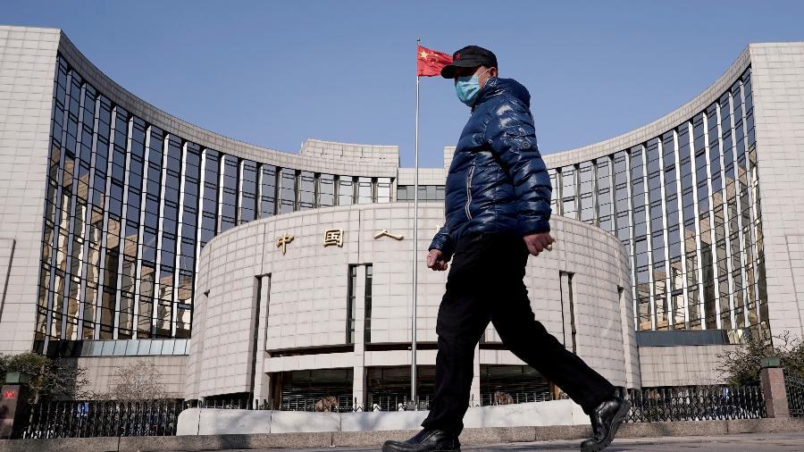 Homem usando máscara caminha na região do Banco Popular da China, em Beijing - REUTERS/Jason Lee