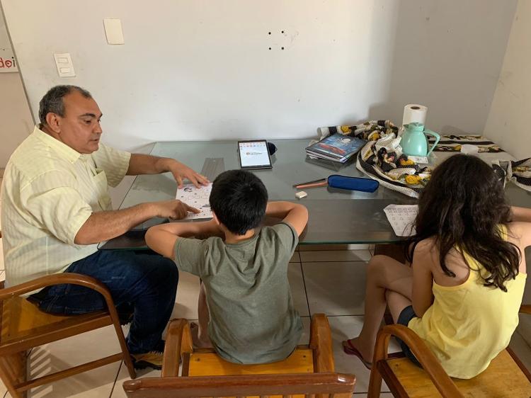 Guilherme, 9 anos, e Laura, 10 anos, fazem as atividades escolares com a ajuda do pai em casa  - Ana Paula Bimbati/UOL - Ana Paula Bimbati/UOL