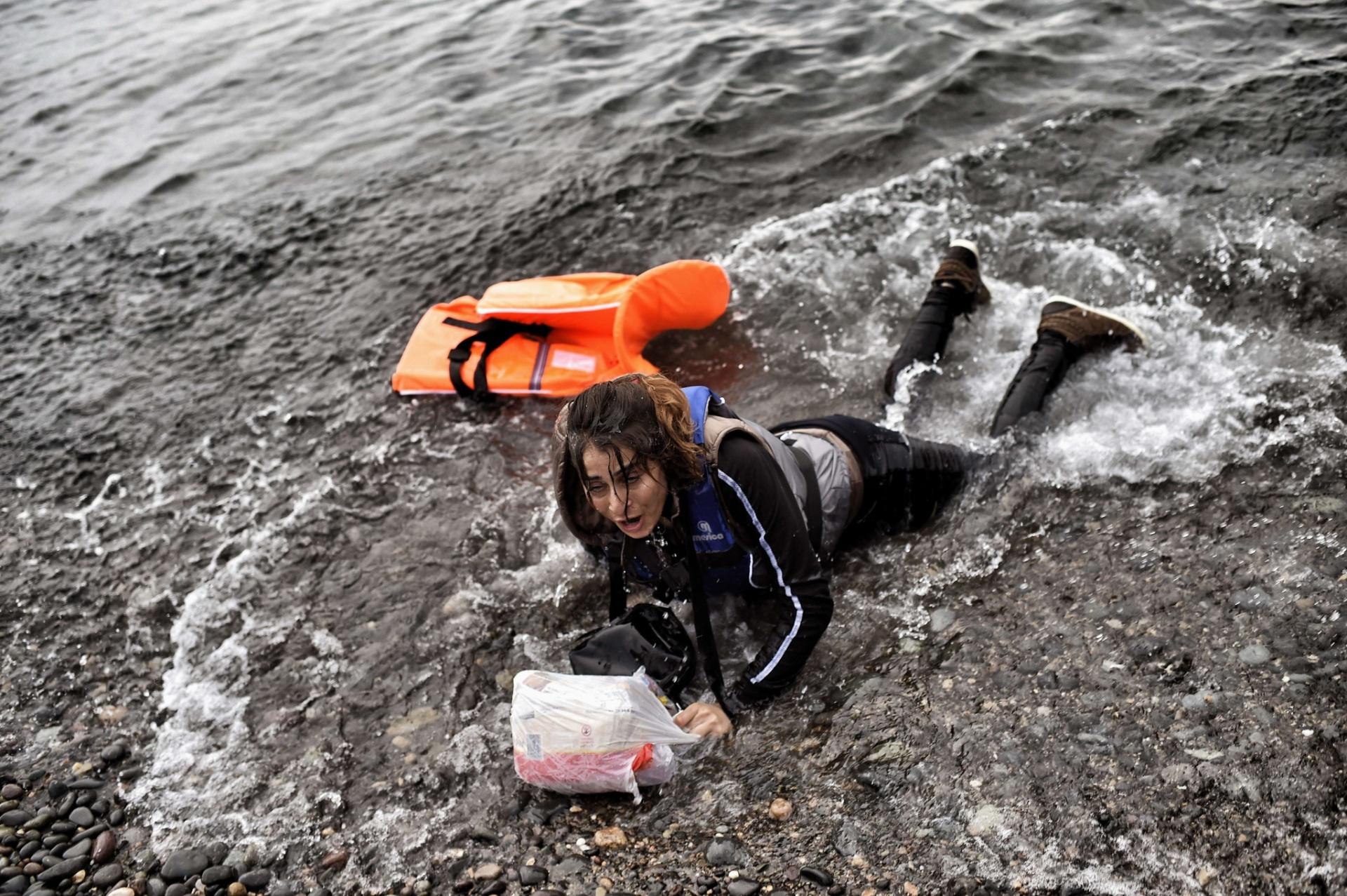 28.set.2015 - Refugiada síria chega a praia da ilha grega de Lesbos depois de atravessar o mar Egeu com o auxílio de um colete salva-vidas. A embarcação em que ela estava afundou e deixou dezenas de mortos