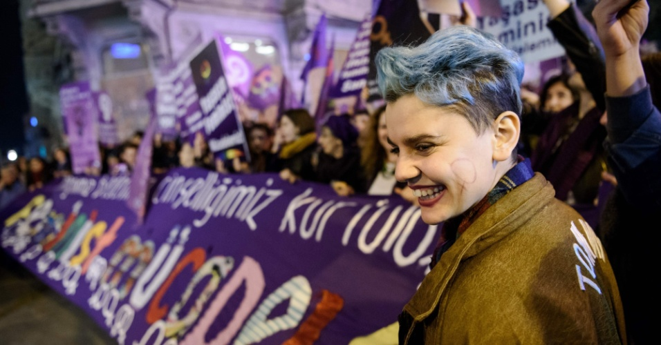 """8.mar.2016 - Em Istambul, na Turquia, uma mulher sorri próxima a uma faixa em que se lê """"luta feminista"""" durante marcha na cidade. Dia Internacional das Mulheres é marcado por protestos feministas por todo o mundo"""