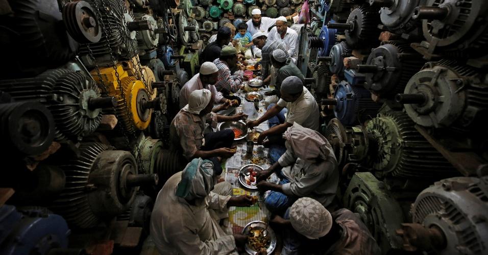 4.jul.2016 - Trabalhadores comem o iftar dentro de uma loja na parte antiga de Déli, na Índia. Eles reparam motores elétricos de segunda mão e bombas d'água