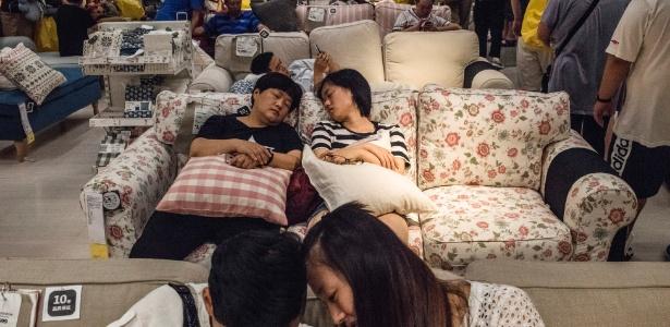 Duas mulheres tiram uma soneca em um sofá que está à venda na Ikea, em Pequim