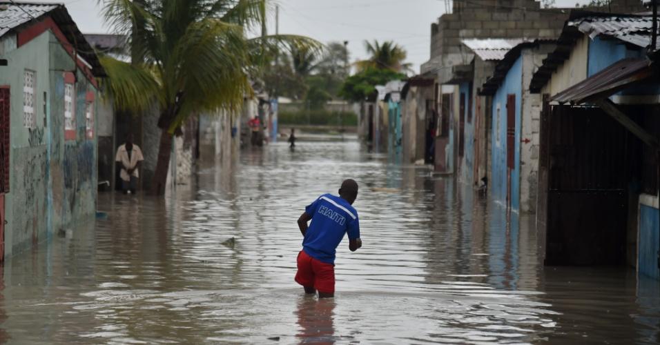 4.out.2016 -Homem caminha por rua alagada na comuna de Cite Soleil, na capital Porto Príncipe, após passagem do furacão Matthew