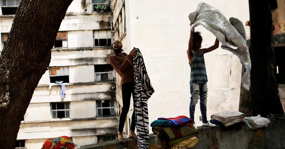8.nov.2016 - Rodrigo (à esquerda), 26, e Wam (à direita), 24, estendem roupas na área externa do prédio ocupado no Centro de São Paulo que serve como refúgio para a comunidade LGBT