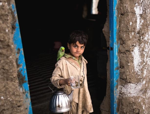 Bilal Shah, 6, e seu papagaio Toti na nova casa da família, no Afeganistão