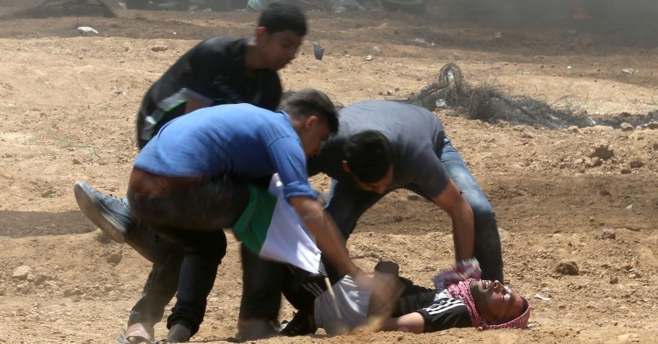 14.mai.2018 - Palestinos ajudam homem ferido em confronto com forças israelenses em Jabalia, na Faixa de Gaza. Palestinos protestam contra a transferência da embaixada dos EUA de Tel Aviv para Jerusalém e contra o 70º aniversário da criação de Israel